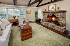 Family room features cathedral ceilings accented by wooden cross beams and ceiling fan. A wood-burning fireplace with raised hearth with a hand-hewn wooden mantle, and fieldstone surround. Doors to kitchen garden and terrace. Doors to deck overlooking backyard and pool area.