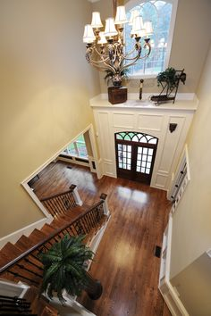 A view of the above foyer from the top of the staircase landing, showing the shelf above the doors, the large light fixture, and the fern topping the dark column. Above Door Decor, Window Ledge Decor, Alcove Decor, Foyer Design, Hall Design, House Design, Plant Ledge Decorating, Foyer Decorating, Front Door Entryway