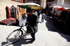 A man pushing his bicycle at a bazaar in the historical city Khiva, Uzbekistan. Radio Ozodlik.