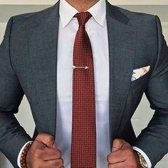 Tie compliments the grey suit