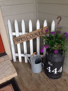 Old picket fence, antique milk can with hanging basket of flowers for front porch decor #farmhousestyle