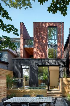 Red Brick And Black-Stained Cedar Siding- Accessed through the door in the kitchen or from the lower living room, the backyard of this modern house is made up of different levels that house a bbq, planters and an outdoor dining area Luxury Kitchen Design, Modern House Design, Red Door House, Toronto Houses, Cedar Siding, Wood Siding, Narrow House, Duplex, Townhouse