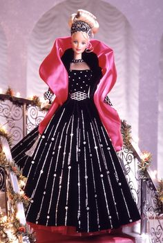 Shop » Special Occasion » Happy Holidays® Series  1998 Happy Holidays® Barbie® Doll  No Longer Available From MattelSpecial Edition   Release Date: 1/1/1998   1998 Happy Holidays® Barbie® doll presents her sophistication and elegance dressed in a holiday theme gown in rich black velvety fabric with exquisite silver glitter accents — she is truly something special as the only doll in the series to wear black. A pink cape and jeweled tiara accent this stunning ensemble. As a