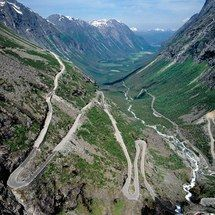 """Trollstigen The name translates to """"Troll's Path"""". The route is known for its 11 hair-raising hairpin turns and steep, 9% gradient. Yet despite the dangers of the one-lane road, it's become a popular tourist attraction, every year before it closes each winter. You definitely shouldn't take your eyes off this road while you're driving, but  if you do you can catch a glimpse of the impressive Kongen (King), Dronningen (Queen), and Bispen (Bishop) mountains, or stop at the 1,050-foot Stigfossen…"""
