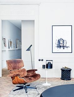 In the sitting room an offertory box from Myanmar and a Moroccan stool contrast with an Eames 'Lounge' chair', Eero Saarinen side table and Arne Jacobsen 'AJ' floor lamp produced by Louis Poulsen; the ink drawing is by Philippe Cognée.