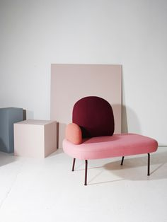 Contemporary sofa chair in dark red, peach and pink fabrics.