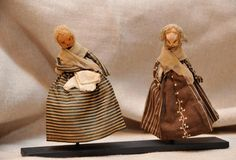 "Chestnut Head Dolls. Rare survivors of children's toys made using a chestnut as the head, and then dressing the bodies in their ""Sunday finest"". Early 19th century.    Teens Silks, patterned cottons, aprons, bonnets, bags, pockets, 4 1/2"" tall, professionally made stand."