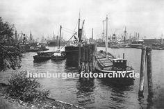 0953984 hamburg Bilder vom Hamburger Hafen Fotos der Hafenstadt -  Blick vom Lübecker Ufer in den Hansahafen - im Hintergrund die Schornsteine der Frachtschiffe die am Oswaldkai liegen und deren Ladung gelöscht wird. Im Vordergrund hölzerne Duckdalben, die aus langen Baumstämmen gerfertigt werden, die tief in den Hafengrund gerammt werden. An ihnen hat ein Motor-Binnenschiff und ein Dampfschiff festgemacht - das Binnenschiff hat seine Ladeluken mit Brettern abgedeckt, die die Ladung schützen…