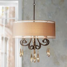 From the Kathy Ireland chandelier collection, this bronze finish scrolled pendant light features champagne crystal accents and a tan brown double shade.