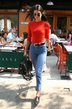 The model is seen leaving an NYC restaurant wearing high waisted jeans embellished with a statement belt, a bright three-quarter sleeve shirt, oxfords, and a leather satchel.