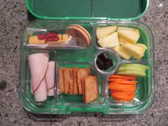 Yumbox Lunch - cheese strings - white oreo cookie - oven roasted turkey - triscuit crackers - carrot and cucumber slices - pineapple - fruit snacks