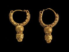 Roman gold hoop earrings, 1st-2nd century A.D. Nabatean, Jordanian. The earrings are composed of two elements, the hoop, which was inserted into the earlobe and the pendant fixed to the underside of the ring. The hoop is a circular wire with the clasp at the top, it is decoratedwith a series of small cast spheres. The pendant was formed from two spheres positioned vertically and separated by a granulated frieze with some geometric motifs, 6.7 cm long. Private collection
