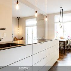 Tolle offene Küche in weiß! Der Küchenblock geht optisch in den Esstisch über. Eingerichtet von BESPOKE Stefan Neubrand Innenarchitekten aus München.