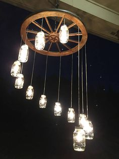 Your place to buy and sell all things handmade Spiral Wagon Wheel Mason Jar Chandelier (large) Mason Jar Chandelier, Rustic Chandelier, Mason Jar Lighting, Wagon Wheel Chandelier Diy, Quart Size Mason Jars, Mason Jar Diy, Pots Mason, Hanging Jars, Hanging Lights