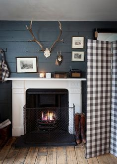 navy, antlers, hunting lodge style; paint inner fireplace panel navy or black; stone or dark tile in floor in front of fireplace