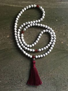 Our white and red mala is crafted of natural howlite, containing a variety of grey veins, and dark red carnelian spacers. Each spacer is set off with pewter rondelles, and spacers are set after sections of 27. There are 108 8mm howlite beads, and the mala is finished with a carnelian