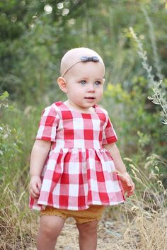 Tunic topfor girls features 3 buttons on the back, and bold red checked linen fabric. *Runs BIG, size down at least one size to fit more as a tunic/top. Model