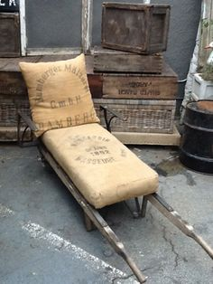 An old crate dolly with steel added for arms, cushion covered in French grain sack. HOW. COOL.
