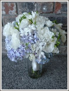 blue hydrangeas bouquet with roses, lisianthus and stephanotis.  This is a bridal bqt in water, waiting for the bride.