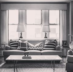 Couch in front of 3 windows. Like the two curtians and the two lamps behind.