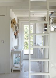 a ladder leads up to the bedrooom in this miniature whitewashed beach house