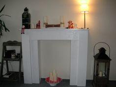 Weiße Kaminattrappe vor beiger Wand mit Dekorationen aus Kerzen, Lampen und Weihnchtsdeko