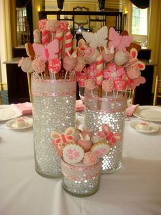 christening centerpieces made from tall cylinder vases, water beads, and lots of sweets. Follow us for more planning inspiration or contact us at www.tidesevents.co.uk for help planning your party.