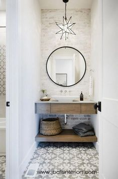 fun modern farmhouse bathroom with floating wood vanity and cement tile floor with round mirror over bathroom vanity and star pendant light, modern farmhouse powder room design