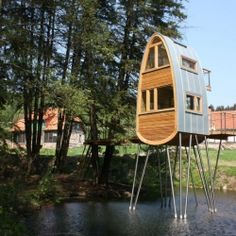 Beautiful treehouse elevated over pool of water in Germany.