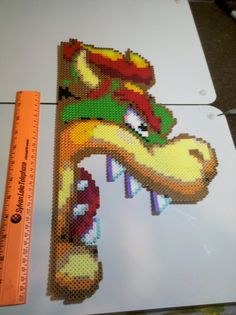 Bowser Perler Bead Art Going to hang him up so that he is poking out from behind my cabinets. My first real perler bead project. Perler Bead Designs, Hama Beads Design, Perler Bead Mario, Perler Bead Disney, Melty Bead Patterns, Beading Patterns, Fuse Beads, Perler Beads, Yoshi