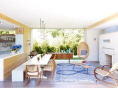 une cuisine sociale et moderne avec une table à manger blanche et un demi-mur