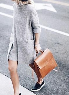 A sweater dress, sneakers, and a leather bag.