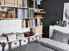 Eine Wand mit ALGOT Regalböden in Weiß voller Bücher und Aufbewahrungsboxen. Daneben das Bett.
