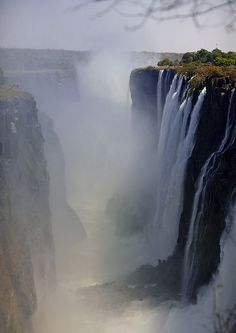 Africa |  Victoria falls photographed from the Zambian side |  © Eric Lafforgue  { The Victoria falls is 1 708 meters wide, making it the largest curtain of water in the world. It drops between 90m and 107m into the Zambezi Gorge and an average of 550,000 cubic metres of water plummet over the edge every minute. }