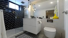 In their master ensuite, the pair went for a black tiled feature wall with a pop of colour in the accessories.