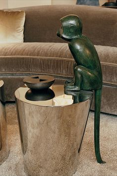 A bronze monkey by Francois-Xavier Lalanne perched atop a stainless-steel cocktail table.