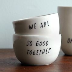 "A set of two hand-thrown porcelain cellars covered in a clear gloss glaze with black lettering. One vessel reads ""We are"" and the other ""So Good together"" , Shanna Murray"