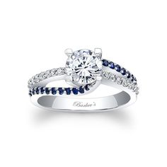 A classic design with a unique flair, this blue sapphire and diamond engagement ring features a prong set round diamond center. The shank is adorned with a ridge of shared prong set blue sapphires swirling on opposing ridges, while a ridge of white diamonds appears to run through the middle for an elegant touch of drama. Also available in 18k and Platinum.