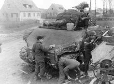 L'équipage d'un M4 Sherman applique une couche de ciment à l'armure frontale du char afin d'augmenter ses capacités d'arrêt. Le 19 mars 1945 à Gelsenkirchen en Allemagne.