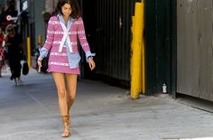 Leandra Medine wears a blue button-down shirt, matching jacket and skirt, and lace-up sandals
