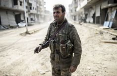 A Kurdish fighter stands in the center of <span>Kobani, after it was recaptured from ISIS militants, </span>on January 28.