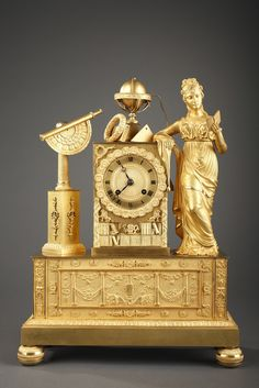 An interesting gilt bronze mantel clock with a complex iconography on the theme of arts and sciences. On the right side, a young woman wearing an Empire dress and on...
