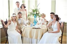 Gatsby Party Styled Shoot Blue gold art deco feather pearls table setting. Bridal party pose. Vintage theme. Tall bouquets, back lighting.
