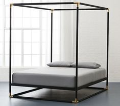 A canopy bed frame that elevates any mattress to posh executive suite level. | 33 Products That Will Turn Your House Into A Minimalist Dream