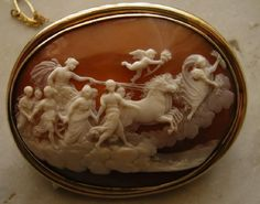 Aurora's Chariot Shell Cameo in Gold Frame | c.1850/60 | Italy | sardonyx shell,15k yellow gold | Overall: 2 5/8 in x 2 1/8 in | after a fresco by Guido Reni in the Casino, Palazzo Pallavicini-Rospiglios, Rome c.1614 | detailed work depicts Aurora, goddess of dawn, leading a procession, showering roses on a still sleeping earth followed by 4 galloping horses & Apollo's chariot, 7 Horae (hours) & a cherub holding a flaming torch personifies the morning star. Below are trees & ancient bldgs.|