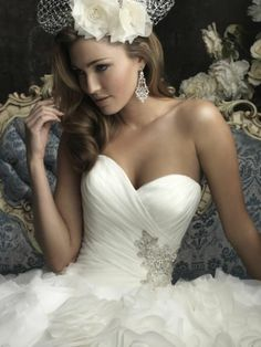 A fitted Wedding Dress featuring a sweetheart neckline and beautiful organza that wraps asymmetrically throughout the bodice with Swarovski crystals accenting the waistline.
