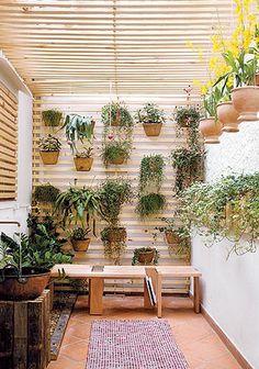 Vasos com véu-de-noiva, chifre-de-veado, bromélia e peixinho foram acomodados na treliça de madeira da parede, em um painel vertical