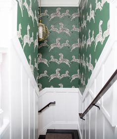 Amazing staircase features upper part of walls clad in Serengeti Green Scalamandre Zebra Wallpaper and lower walls clad in board and batten trim illuminated by a brass pierced globe pendant, Currey & Co Tartufo Chandelier.