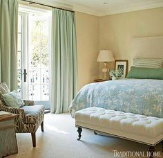 Soothing greens, blues, and creams in the bedroom create a peaceful reverie. A tufted settee at the foot of the bed adds a touch of traditional among the patterned fabrics at the bed and chair.