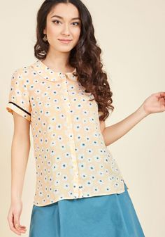 """When your bestie calls to consult on today's dress code, you choose """"ladylike"""" with this ModCloth namesake label blouse in mind! Pairing a Peter Pan collar with ribbon-trimmed short sleeves, and patterned with pastel pink, ivory, and navy flowers, this pale yellow button up brings vintage-inspired charm into the limelight."""